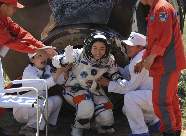 In this photo released by China's Xinhua news agency, China's first female astronaut Liu Yang waves as she comes out of the re-entry capsule of Shenzhou-9 spacecraft in Siziwang Banner of north China'
