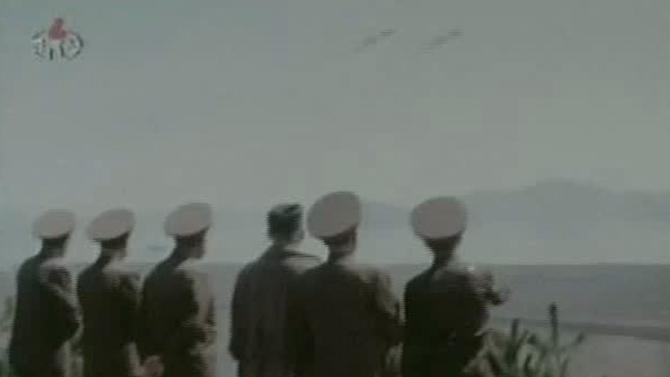 """In this undated image made from KRT video, North Korea's new young leader Kim Jong Un, third from right, watches jet fighters fly in the sky with North Korean officials at an undisclosed place in North Korea, aired Sunday, Jan. 8, 2012. Kim Jong Un, who was named """"supreme leader"""" of North Korea's people, ruling Workers' Party and military following the death last month of his father, Kim Jong Il, was shown observing firing exercises and posing for photographs with soldiers in footage that was shot before his father's death and aired as a documentary Sunday. (AP Photo/KRT via APTN) TV OUT, NORTH KOREA OUT"""