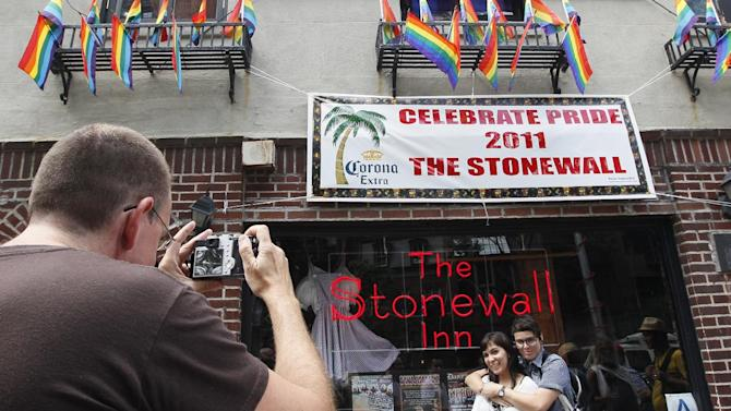 FILE - In this June 25, 2011 file photo Audrey Berry, left, and Paxx Moll, right, have their picture taken in front of the Stonewall Inn in New York. The National Park Service is launching an initiative to make places and people of significance to the history of lesbian, gay, transgender and bisexual Americans part of the national narrative. (AP Photo/Mary Altaffer,File)