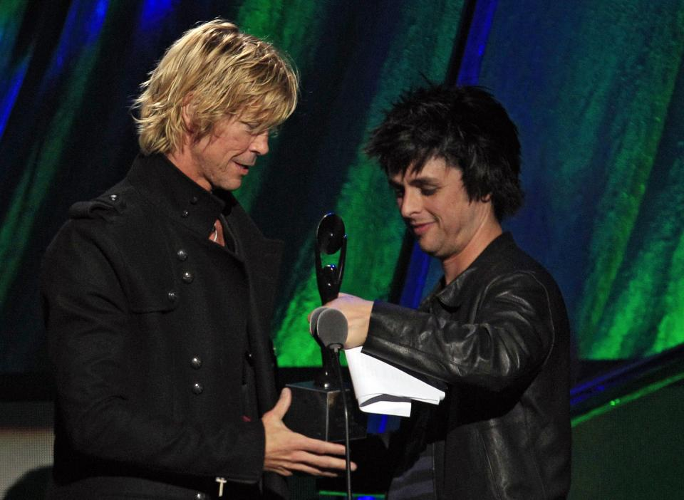 Guns N' Roses' Duff McKagan, left, accepts his trophy from Green Day's Billy Joe Armstrong after Guns N' Roses was inducted into the Rock and Roll Hall of Fame Saturday, April 14, 2012, in Cleveland. (AP Photo/Tony Dejak)