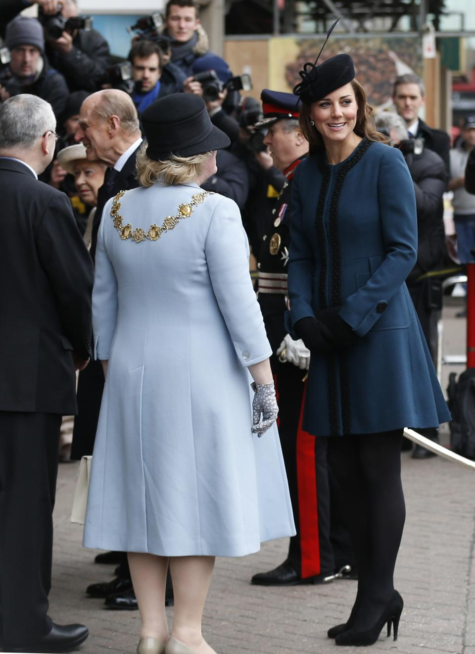Britain's Kate, Duchess of Cambridge, right, accompanies Queen Elizabeth II and Prince Philip, obscured at left, as they arrive at Baker Street underground station in London for a visit to mark the 150th anniversary of the London Underground, Wednesday, March 20, 2013. (AP Photo/Sang Tan)