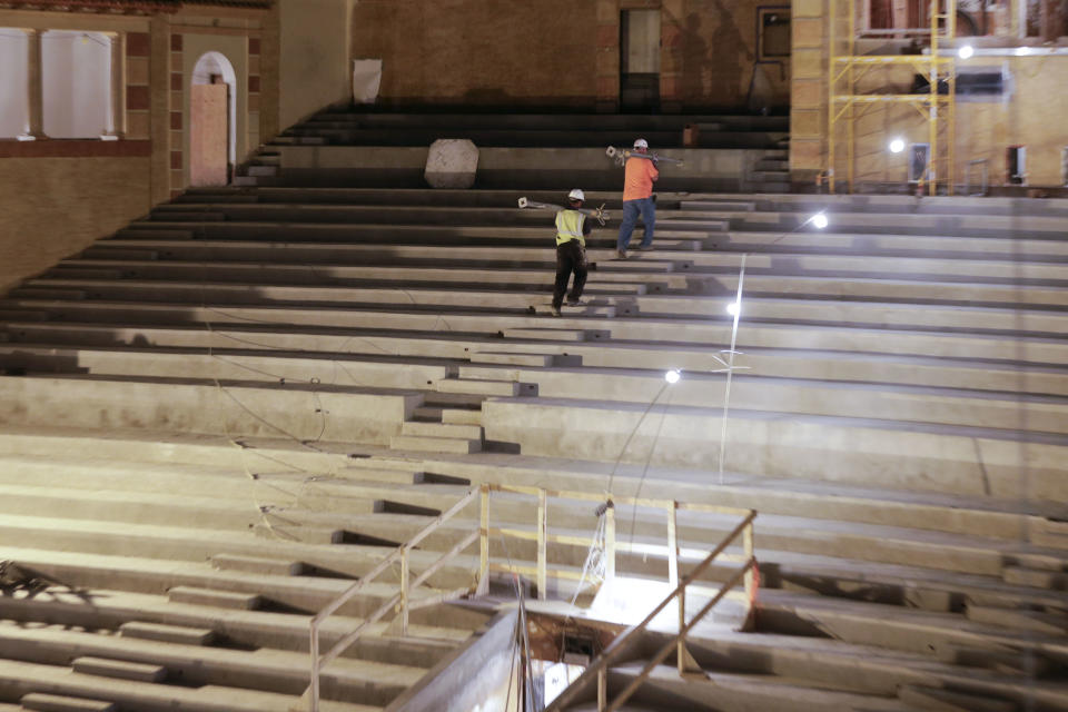 Workers walk up stairs during the restoration of the Saenger Theater in Downtown New Orleans on Wednesday, May 22, 2013. (AP Photo/Gerald Herbert)