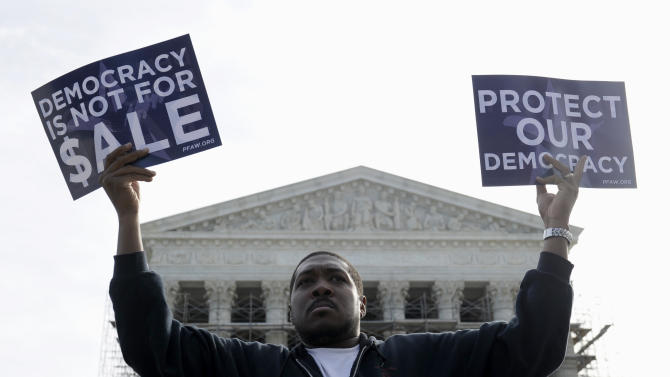 """FILE - This Oct. 8, 2013, file photo shows Cornell Woolridge of Windsor Mill, Md., as he demonstration outside the Supreme Court in Washington, as the court heard arguments on campaign finance. The first midterm elections since both parties embraced a historic change in campaign finance, and with it a sea of campaign cash, will mean for most voters an avalanche of television ads trying to reach the few able to be swayed and willing to vote. In the nation's closest races for U.S. Senate, that translates into """"price per vote"""" that could easily double what was spent in the 2012 presidential election. (AP Photo/Susan Walsh, File)"""