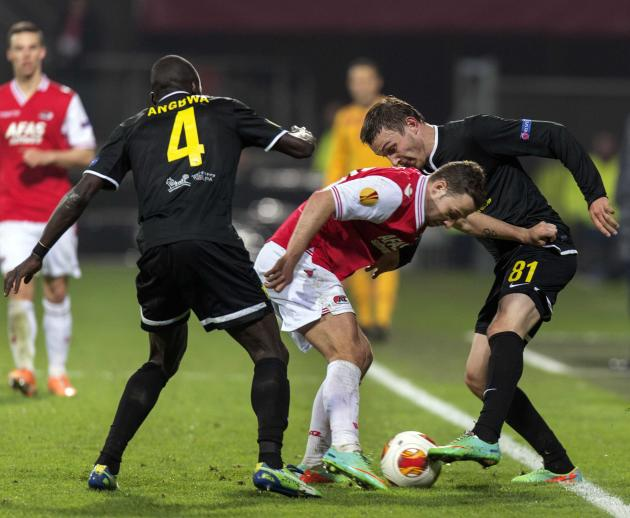 AZ Alkmaar's Roy Beerens fights for the ball with Anzhi Makhachkala's Nikita Burmistrov and Benoit Angbwa during their Europa League soccer match in Alkmaar