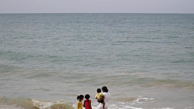 The family of a victim look out to sea on the 10th anniversary of the Indian Ocean tsunami in Pereliya
