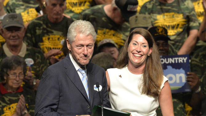Former President Bill Clinton, left, is introduced to the audience by Kentucky Democratic Senatorial candidate Alison Lundergan Grimes before addressing a group of supporters during a political rally, Wednesday, Aug. 8, 2014, at the Hal Rogers Center in Hazard, Ky. Seated behind Clinton, are members of the United Mine Workers Association, whose union has endorsed Grimes. (AP Photo/Timothy D. Easley)
