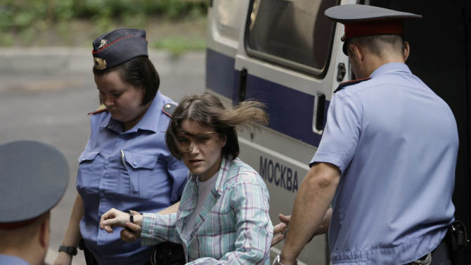 """Maria Alekhina, center, a member of feminist punk group Pussy Riot is escorted to a court room in Moscow, Russia, Monday, July 30, 2012. Three members of the band are facing trial for performing a """"punk prayer"""" against Vladimir Putin from a pulpit of Moscow's main cathedral before Russia's presidential election in March, in which he won a third term. (AP Photo/Mikhail Metzel)"""