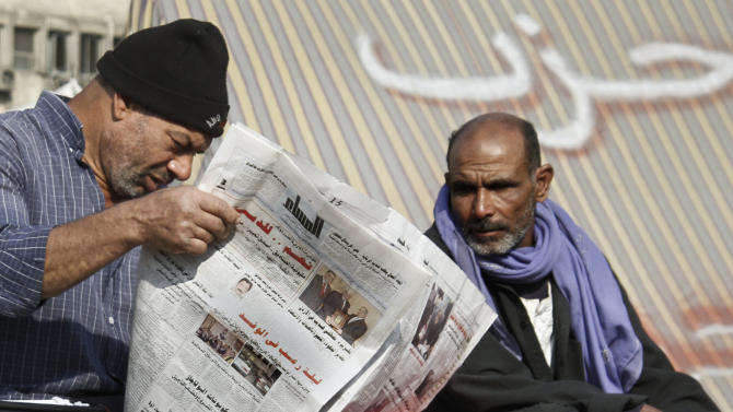"An Egyptians protester reads a newspaper in Tahrir Square, the focal point of the Egyptian uprising, in Cairo, Sunday, Dec.16, 2012. Key Egyptian rights groups called Sunday for a repeat of the first round of the constitutional referendum, alleging the vote was marred by widespread violations. Islamists who back the disputed charter claimed they were in the lead with a majority of ""yes"" votes. Arabic on the tent, background, reads, ""party."" (AP Photo/Amr Nabil)"