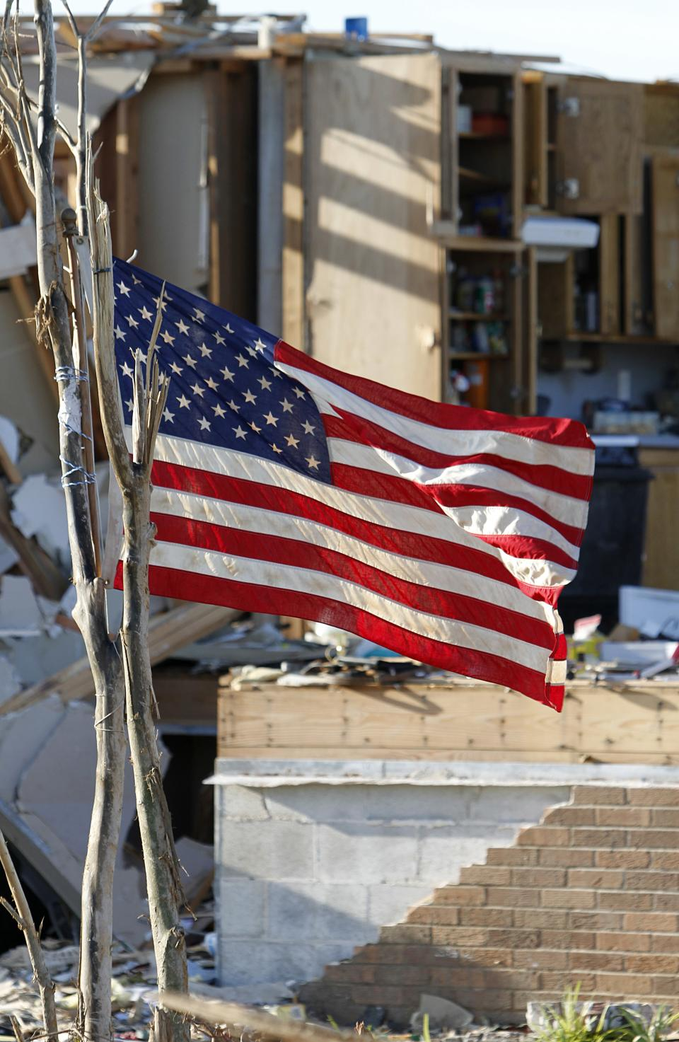 An American flag waves in the wind in front of a house, Thursday, May 5, 2011, that was destroyed when a tornado ripped through the area last week in Pleasant Grove, Ala. (AP Photo/Butch Dill)