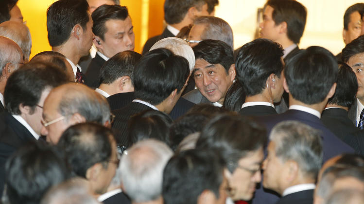 Japanese Prime Minister Shinzo Abe, center, talks with business leaders during Japan's business organizations joint New Year's party in Tokyo,  Monday, Jan. 7, 2013. Asian stocks cooled off Monday as some investors sold shares to lock in profits following recent rallies. (AP Photo/Shizuo Kambayashi)