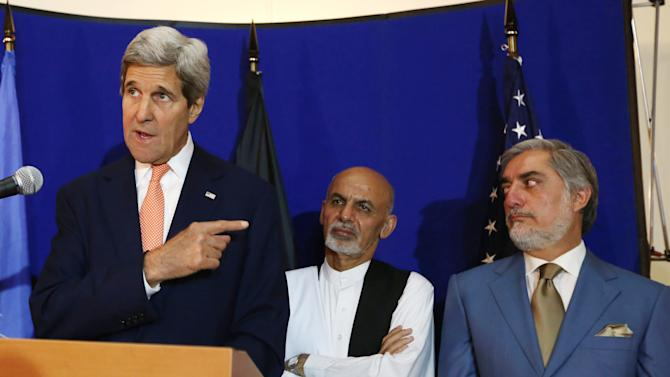 FILE - In this Friday, Aug. 8, 2014 file photo, U.S. Secretary of State John Kerry, from left, speaks as Afghan presidential candidates Ashraf Ghani Ahmadzai and Abdullah Abdullah listen during a joint press conference in Kabul. Afghanistan's two presidential candidates were set to a sign a power-sharing deal on national TV on Sunday, three months after a disputed runoff that threatened to plunge the country into turmoil and complicate the withdrawal of U.S. and foreign troops. (AP Photo/Rahmat Gul, File)