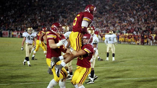 FILE - In this Nov. 30, 1996, file photo, Southern California's Travis Claridge, left, and Mike Bastianelli, right, celebrate with Rodney Sermons (5) after Sermons scored the winning touchdown against Notre Dame in overtime of an NCAA college football game in Los Angeles. Sermons caught a 5-yard touchdown pass from Brad Otton to give Southern California the 27-20 victory. The Associated Press takes a look at some of the memorable games in college football's greatest intersectional rivalry in anticipation of Southern California hosting No. 1 Notre Dame on Saturday, Nov. 24, 2012. (AP Photo/Chris Pizzello, File)