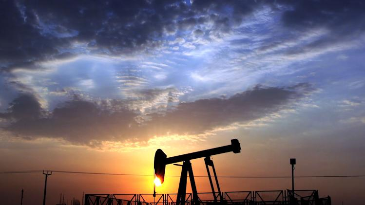 FILE - In this Monday Oct. 29, 2012, file photo, an oil pump operates in the desert oil fields of Sakhir, Bahrain, at sunset. New troves of oil are being found all over the globe and each barrel produced is selling for more than $100, as of Thursday, Aug. 1, 2013. But profits and production at the world's biggest oil companies are slumping badly. (AP Photo/Hasan Jamali, File)
