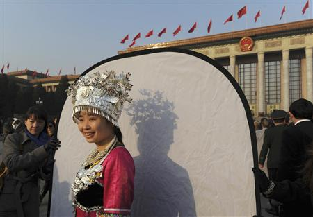 An ethnic minority woman in traditional costume pose for pictures for media ahead of the opening ceremony of the National People's Congress at the Tiananmen Square in Beijing