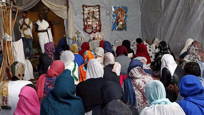 """Christian migrants from Eritrea and Ethiopia pray  during the Sunday mass at the makeshift church in """"The New Jungle"""" near Calais"""