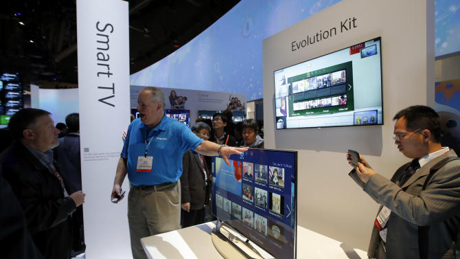Show attendees check out Samsung smart TVs at the Samsung booth at the International Consumer Electronics Show in Las Vegas, Tuesday, Jan. 8, 2013. (AP Photo/Jae C. Hong)
