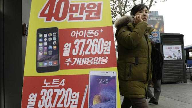 An advertisement poster shows Apple's iPhone 6 Plus, top,  and Samsung Electronics' Galaxy NOTE 4 at a mobile phone shop in Seoul, South Korea, Thursday, Jan. 29, 2015. Samsung Electronics Co. said Thursday its quarterly earnings dropped smaller-than-expected 27 percent in the fourth quarter but its forecast-beating profit could not mask that it was losing the battle of the big phones with Apple Inc. (AP Photo/Ahn Young-joon)