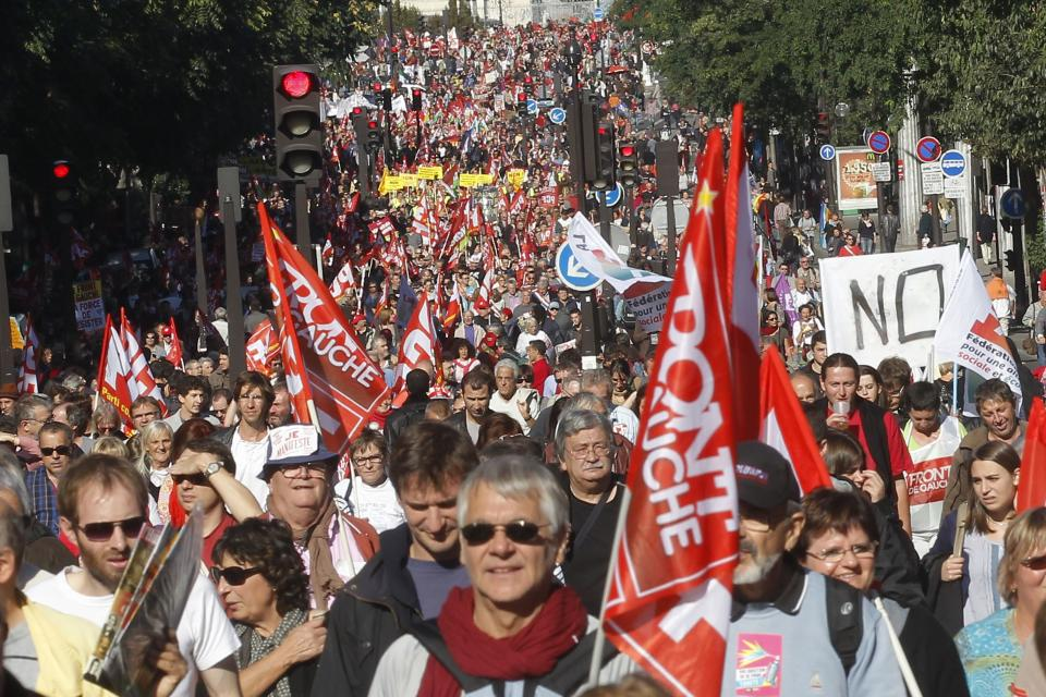 Demonstrators march during a rally with banners and flags to protest against the austerity measures announced by the French government, in Paris, Sunday, Sept 30, 2012. (AP Photo/Michel Euler)