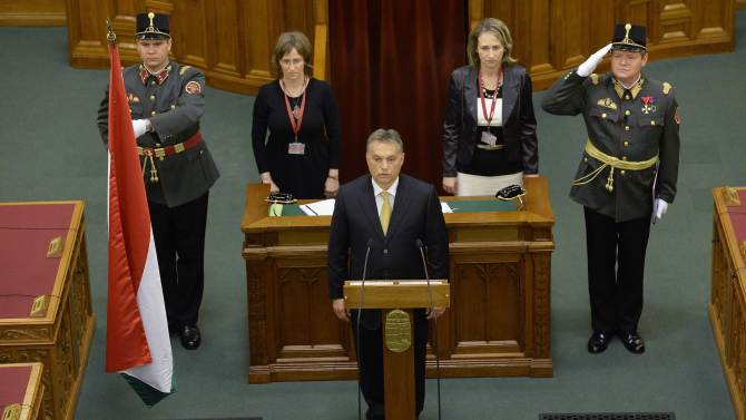 Incumbent Hungarian Prime Minister Viktor Orban, center, swears in after he was reelected by the majority of MPs during a session of the Parliament in Budapest, Hungary, Saturday, May 10, 2014. Orban's reelection comes after his centre-right Fidesz party won a two third majority in the parliamentary elections last April. (AP Photo/MTI, Lajos Soos)