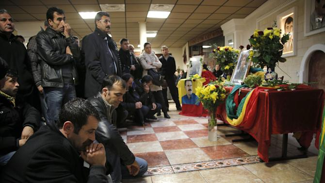 """Men react inside the Kurdish cultural center in Paris, Thursday, Jan. 10, 2013. Three Kurdish women including Sakine Cansiz one of the founders of a militant group battling Turkish troops since 1984, were """"executed"""" at a Kurdish center in Paris, the interior minister said Thursday. (AP Photo/Christophe Ena)"""