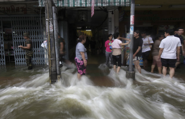 Residents stand as water from the swollen Chao Phraya River flows through a shopping center, located on its bank, in Bangkok, Thailand, Saturday, Oct. 29, 2011. (AP Photo/Altaf Qadri)