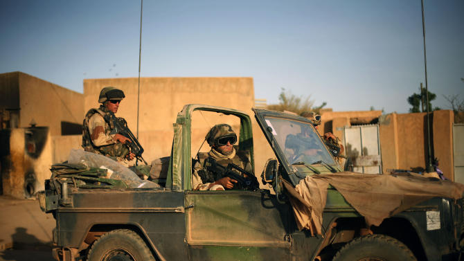 FILE - This Feb. 10, 2013, file photo shows French soldiers securing the evacuation of foreigners during exchanges of fire with jihadists in Gao, northern Mali. Promises of a pullout of France's 4,000 troops in Mali starting next month are looking harder and harder to fulfill. The fighting in rugged mountain terrain is growing tougher and threats of suicide bombings and hostage-takings are getting worse.  (AP Photo/Jerome Delay, File)