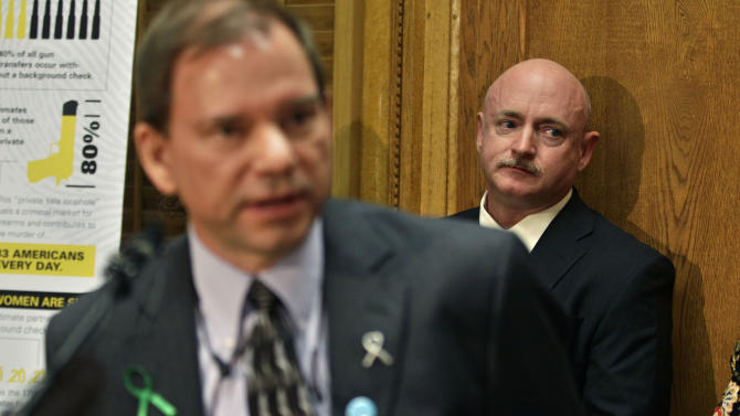 Mark Kelly, husband of former U.S. Rep. Gabrielle Giffords,  listens to Tom Mauser, the father of Columbine High School shooting victim Daniel Mauser, speak during a news conference in favor of proposed gun control legislation at the State Capitol, in Denver, Monday March 4, 2013. State Senate committees began work Monday on a package of gun-control measures that already have cleared the House which include limits on ammunition magazine sizes and expanded background checks to include private sales and online purchases. (AP Photo/Brennan Linsley)