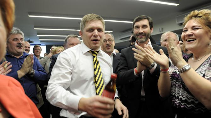 Robert Fico, center, chairman of the Smer-Social Democrats (Smer-SD) celebrates with party members in the early morning on Sunday, March 11, 2012, in Bratislava, Slovakia, after the party won the early elections on Saturday with a comfortable majority in parliament sufficient to form a one-colour government. This will be the first time since the fall of communism in 1989 that one party will control parliament. Fico offered other parties the formation of a coalition government, but it is expected that the left-wing Smer-SD will eventually form a government alone. (AP Photo/CTK, Jano Koller)