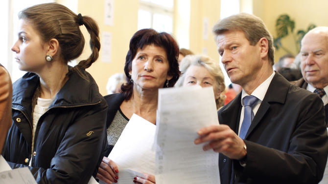 Order and Justice party leader Rolandas Paksas, right, and his wife Laima, center, queue to cast their ballots at a polling station in Vilnius, Lithuania, Sunday, Oct. 14, 2012. Lithuanians are expected to deal a double-blow to the incumbent conservative government in national elections Sunday by handing a victory to opposition leftists and populists and saying 'no' to a new nuclear power plant that supporters claim would boost the country's energy independence. (AP Photo/Mindaugas Kulbis)