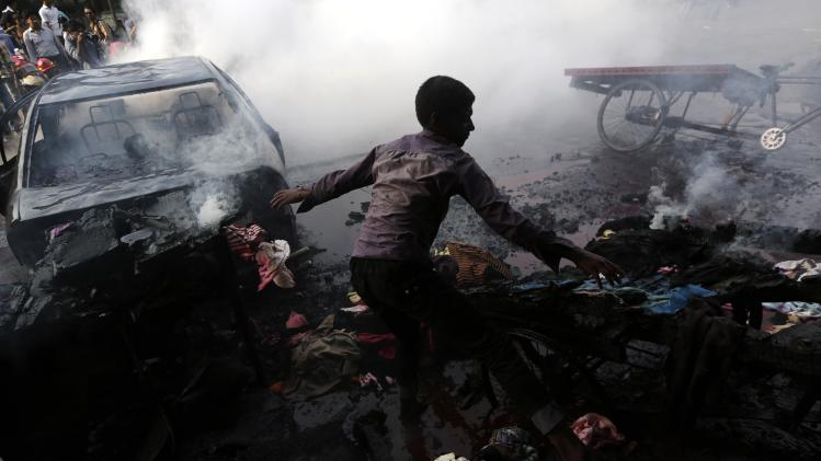 A boy tries to control a fire after vehicles were torched and vandalized by Bangladesh's Jamaat-e-Islami party activists during clashes with police in Dhaka