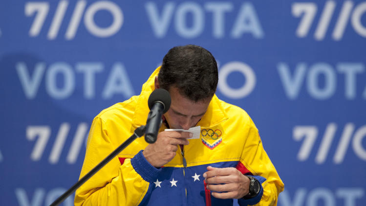 Opposition presidential candidate Henrique Capriles kisses the paper with his notes after he conceded defeat in the presidential elections at his campaign headquarters in Caracas, Venezuela, Sunday, Oct. 7, 2012.  Venezuela's electoral council said late Sunday President Hugo Chavez has won re-election, defeating challenger Henrique Capriles. (AP Photo/Ariana Cubillos)