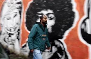 Director Yimer from Ethiopia walks past a mural in downtown Rome