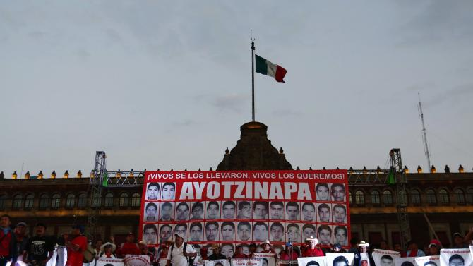 Relatives hold photos of some of the 43 missing trainee teachers of the Ayotzinapa teachers' training college during a demonstration to demand for justice in Mexico City