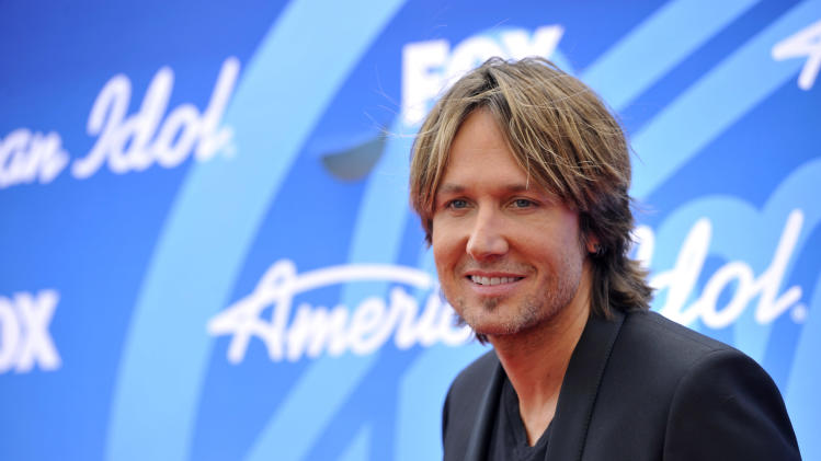 "In this May 16, 2013 photo, Keith Urban arrives at the ""American Idol"" finale at the Nokia Theatre at L.A. Live in Los Angeles. The Australian country music star has set a release date of Sept. 10 for his new album, ""Fuse."" (Photo by Chris Pizzello/Invision/AP)"