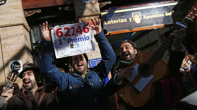 "People sing as they show a poster of the winning number to the first prize of ""El Gordo"" outside a lottery shop where the lottery number was sold in Sanlucar la Mayor, southern Spain"