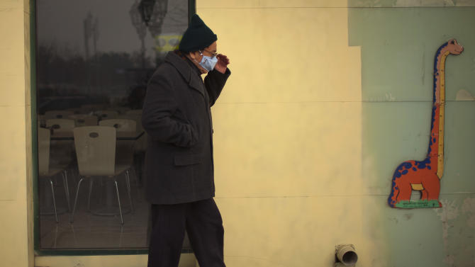 A man wearing a mask walks past a restaurant on a hazy day in Beijing Saturday, Jan. 12, 2013. Air pollution levels in China's notoriously dirty capital were at dangerous levels Saturday, with cloudy skies blocking out visibility and warnings issued for people to remain indoors. (AP Photo/Alexander F. Yuan)