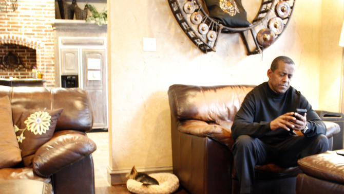 In this image take from video shot on Wednesday, Jan. 25, 2012, Tony Dorsett, a retired Hall of Fame running back for the Dallas Cowboys, reads a text message while sitting in his home in suburban Dallas. Dorsett, 57, is one of at least 300 former players suing the National Football League, claiming the NFL pressured them to play with concussions and other injuries and then failed to help them pay for health care in retirement to deal with those injuries. (AP Photo/Martha Irvine)