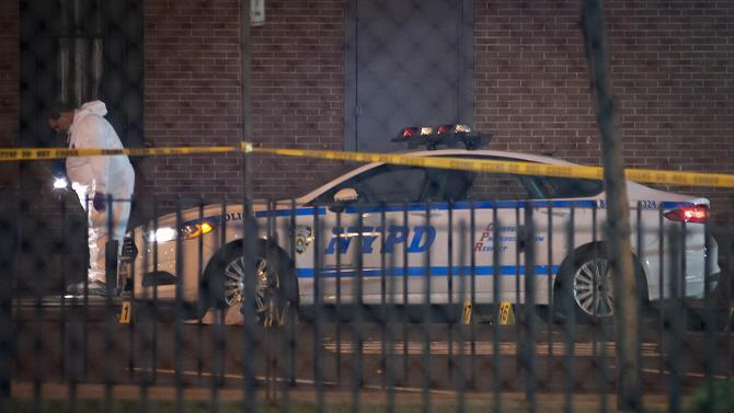 A crime scene investigator examines the scene after two New York Police officers were shot dead in Brooklyn, New York