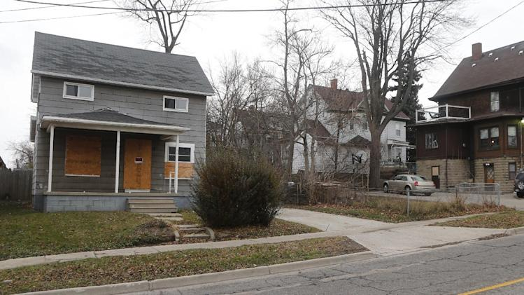 This Dec. 20, 2012 photo shows the house, boarded up at left, in Pontiac, Mich. where James Cotaling was murdered in 1990. (AP Photo/Carlos Osorio)