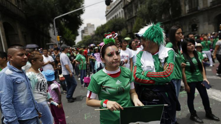 Mexican soccer fans react as they watch the 2014 World Cup soccer match between Mexico and Netherlands during a public viewing at the Zocalo square in downtown Mexico City