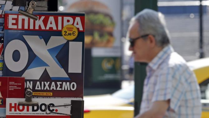 A man walks past newspapers showing the results of yesterday's referendum in central Athens