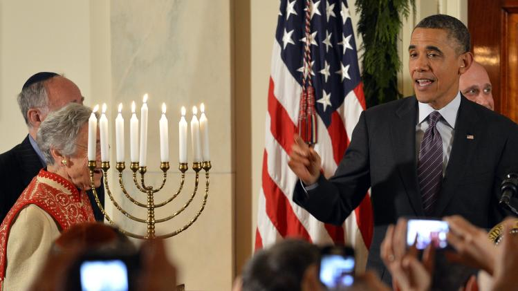 U.S. President Obama makes remarks to guests next to a menorah at the conclusion of a Hanukkah reception, at the White House in Washington