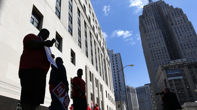 """Firefighters protest outside the Theodore Levin United States Courthouse, in Detroit, Wednesday, July 24, 2013. A lawyer for Detroit argued Wednesday that the city would be """"irreparably harmed"""" if lawsuits challenging a multibillion-dollar bankruptcy are allowed to go forward, the first dispute in the largest municipal bankruptcy in U.S. history. Retirees anxious about their pensions have won favorable rulings from an Ingham County judge that could slow down or even derail the bankruptcy filed just last week.(AP Photo/Paul Sancya)"""