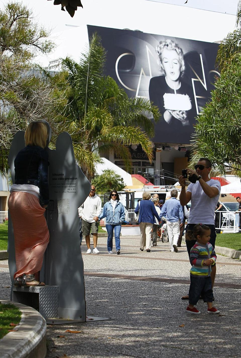 Members of the public take a picture in front of the venue at the 65th international film festival, in Cannes, southern France, Tuesday, May 15, 2012. (AP Photo/Francois Mori)