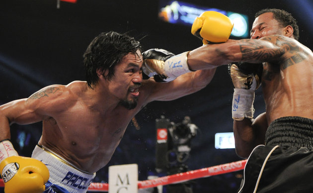 Manny Pacquiao, left, throws a punch against Shane Mosley in the fourth round during a WBO welterweight title bout, Saturday, May 7, 2011, in Las Vegas.  (AP Photo/Mark Terrill)