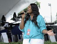 """American Idol 2013 winner Candice Glover sings during a dress rehearsal for PBS's 2013 """"A Capitol Fourth"""" on Capitol Hill in Washington, Wednesday, July 3, 2013. As the nation marks 237 years of independence, thousands of Americans will gather on the National Mall to watch a 17-minute fireworks display and listen to performances by Glover, Barry Manilow, Neil Diamond and John Williams conducting music from the movie """"Lincoln."""" Thunderstorms were in the forecast for the July Fourth celebration in Washington. (AP Photo/Susan Walsh)"""