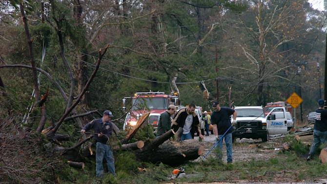 Members of the Alpine Volunteer Fire Department and the VA Fire Department clear debris from U.S. 71 in the Tioga, La. area, after an apparent tornado tore through the area Tuesday, Dec. 25, 2012. (AP Photo/The Daily Town Talk, Melinda Martinez)  NO SALES