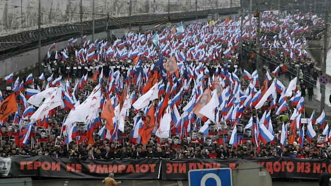 """People carry a huge banner reading 'those bullets for everyone of us, heroes never die!' as they march in memory of opposition leader Boris Nemtsov who was gunned down on Friday, Feb. 27, 2015 near the Kremlin, in Moscow, Russia, Sunday, March 1, 2015. Thousands converged Sunday in central Moscow to mourn veteran liberal politician Boris Nemtsov, whose killing on the streets of the capital has shaken Russia's beleaguered opposition. They carried flowers, portraits and white signs that said """"I am not afraid.""""  (AP Photo/Dmitry Lovetsky)"""