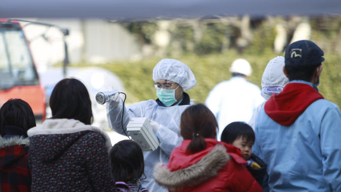 FILE - In this Sunday, March 13, 2011 file photo, residents evacuated from areas surrounding the Fukushima nuclear facilities damaged in Friday's massive earthquake are checked for radiation exposure in Koriyama city, Fukushima prefecture, Japan. The disaster at the Fukushima Dai-ichi nuclear complex in Japan two years ago has heightened worry about how well U.S. communities can protect themselves from a major release of radiation. When a tsunami cut off power and nuclear fuel melted, more than 150,000 people fled the Fukushima area, many from well beyond 12 miles, according to Japan's Education Ministry. U.S. officials recommended that Americans in Japan stay 50 miles back. (AP Photo/Wally Santana)