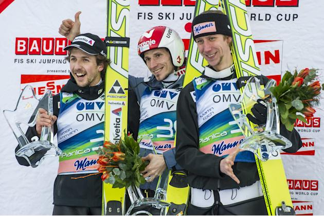Winner Slovenia's Robert Kranjec (C), second-placed Switzerland's Simon Aman (L) and third-placed Austria's Martin Koch (R) pose after the FIS Ski Flying World Cup in Planica on March 16, 2012.  AFP P